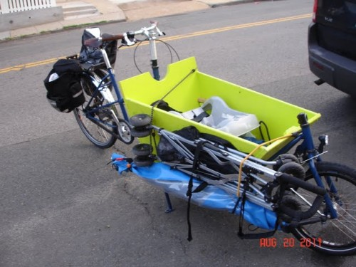 weather canopy and stroller strapped to side of bakfiets